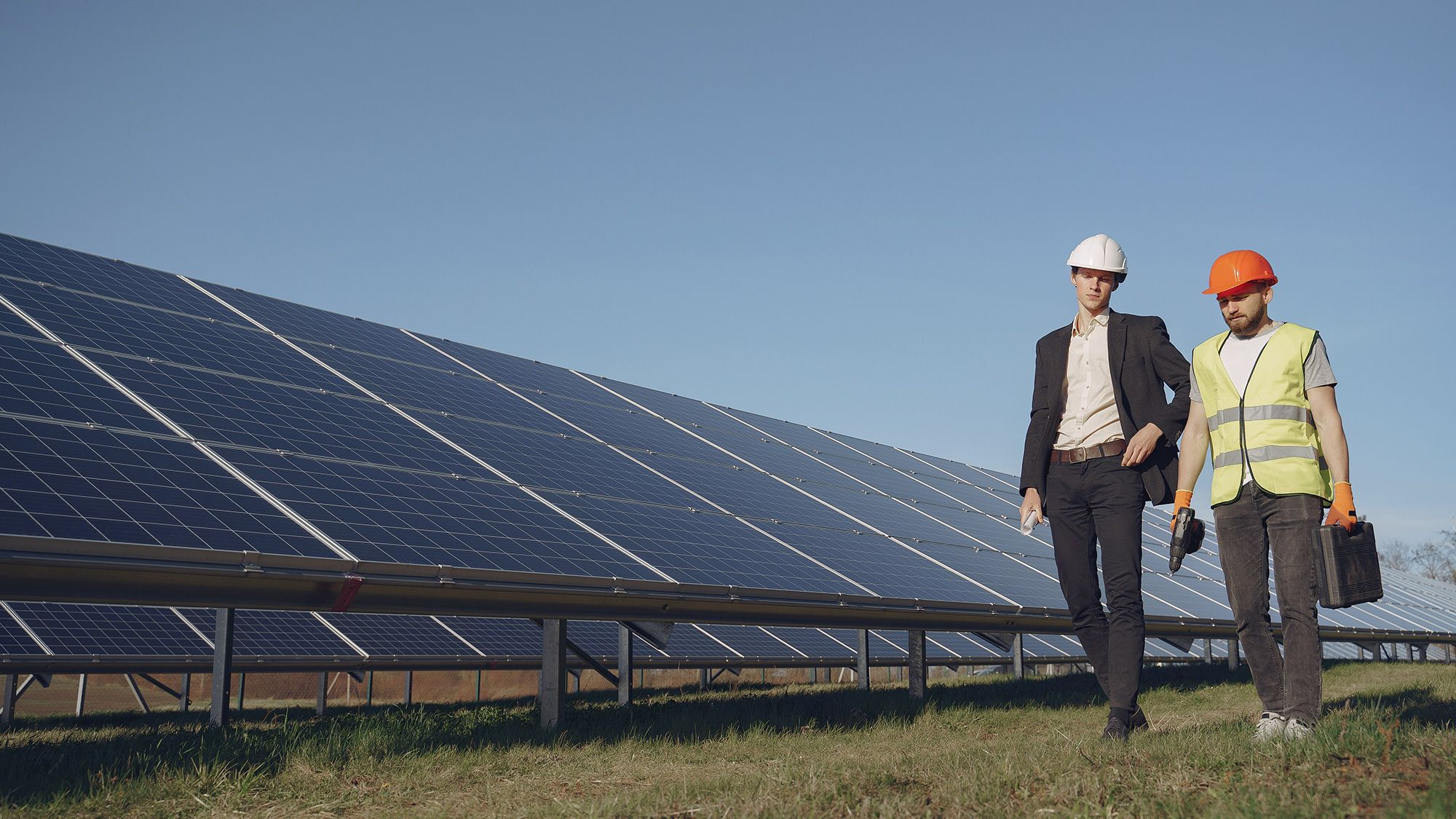 Solar farm engineer talking to a business owner with solar panels in the background